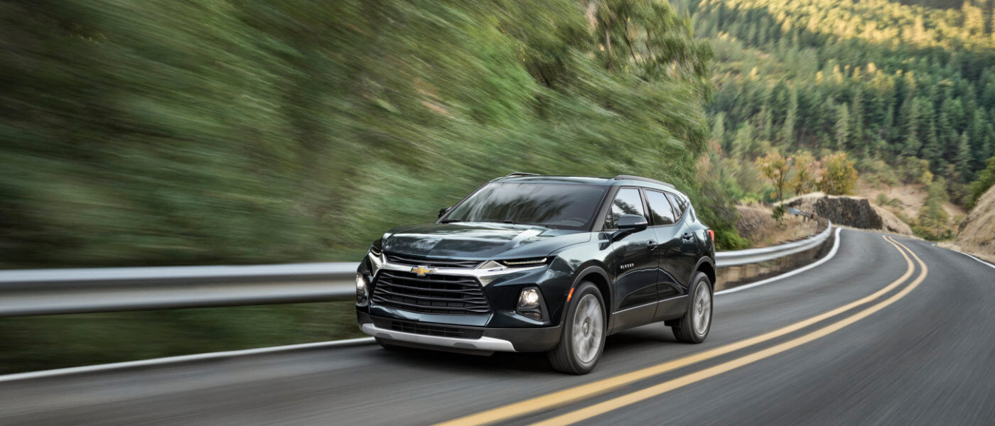 Black 2019 Chevy Blazer driving down the highway in the Forest
