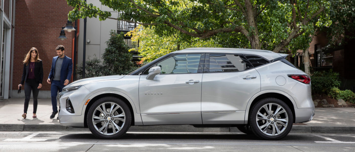 Young couple walking to a Silver 2019 Chevy Blazer parked on the side of the street