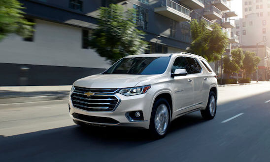 Chevy Traverse white in motion daytime