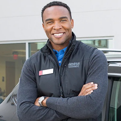 Hendrick employee leaning against a car