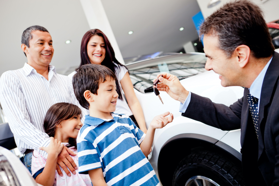 Salesperson handing keys to smiling child