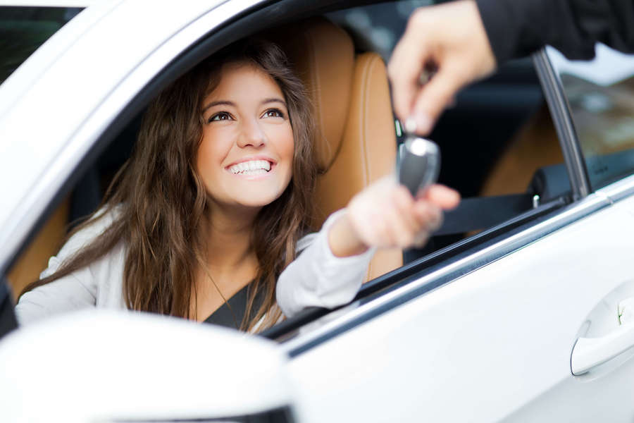 Salesperson handing keys to happy customer sitting in new car