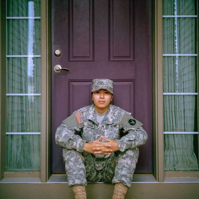 lady in the military in front of her house