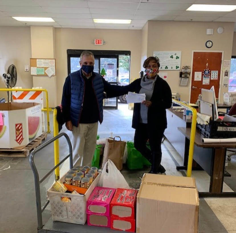 two workers pose together at the food drive