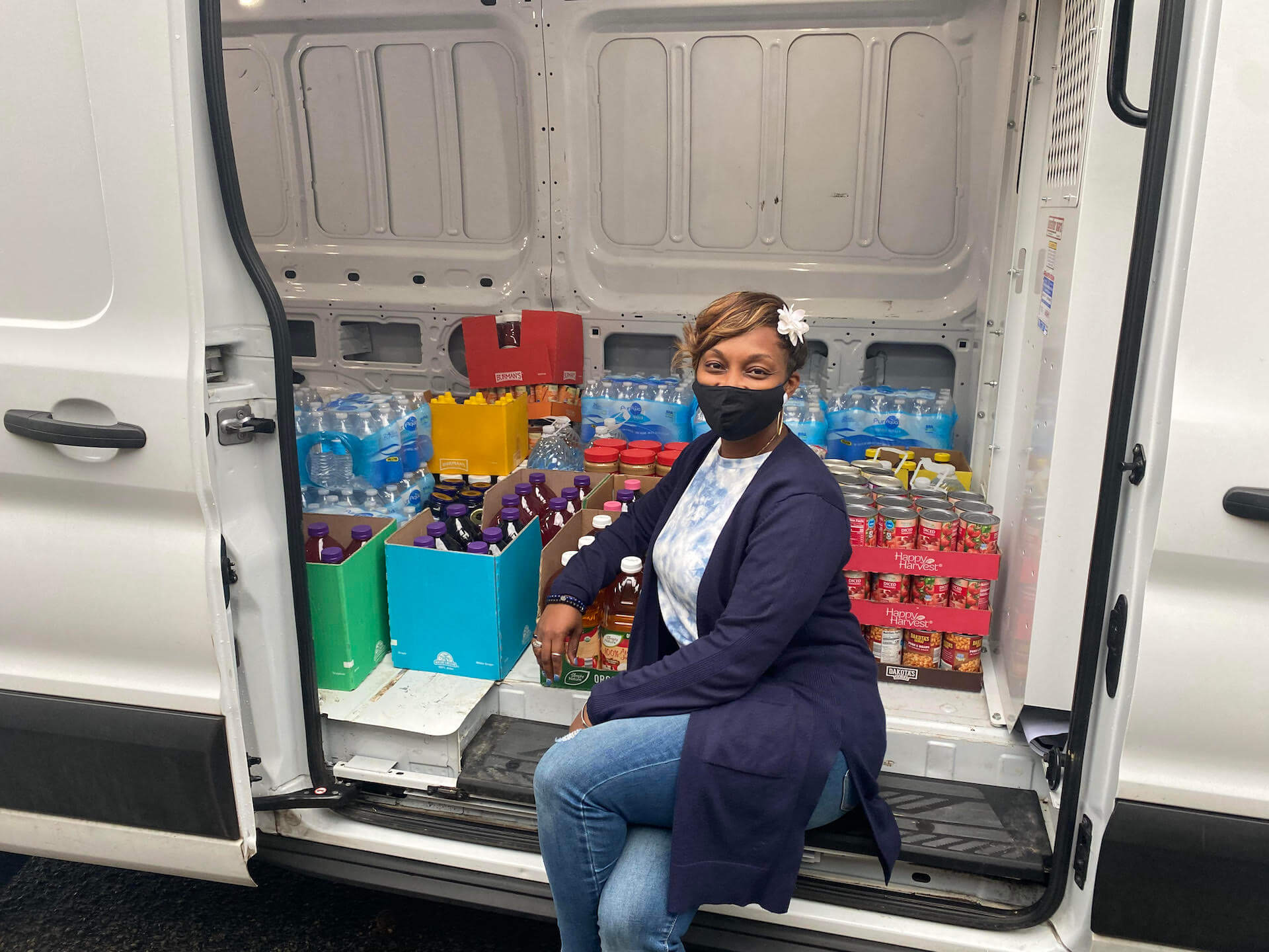 worker in front of all the bottled goods being donated for a food drive