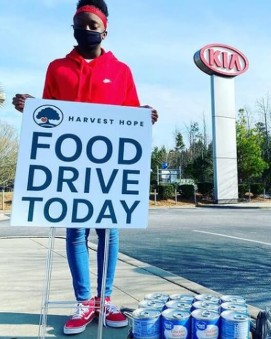 worker holding a sign advertising a food drive