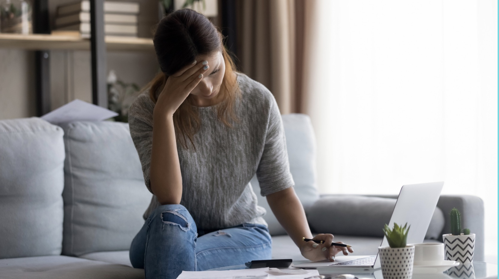 Young professional women paying bills on her computer and stressed about making ends meet.