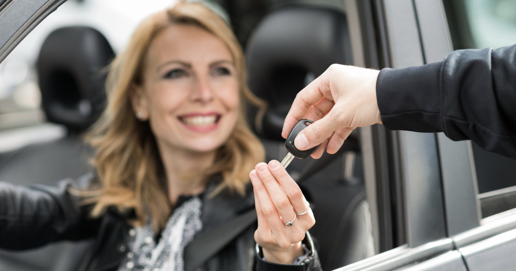 Middle aged woman being handing the keys to a new car she financed in Neptune, NJ.