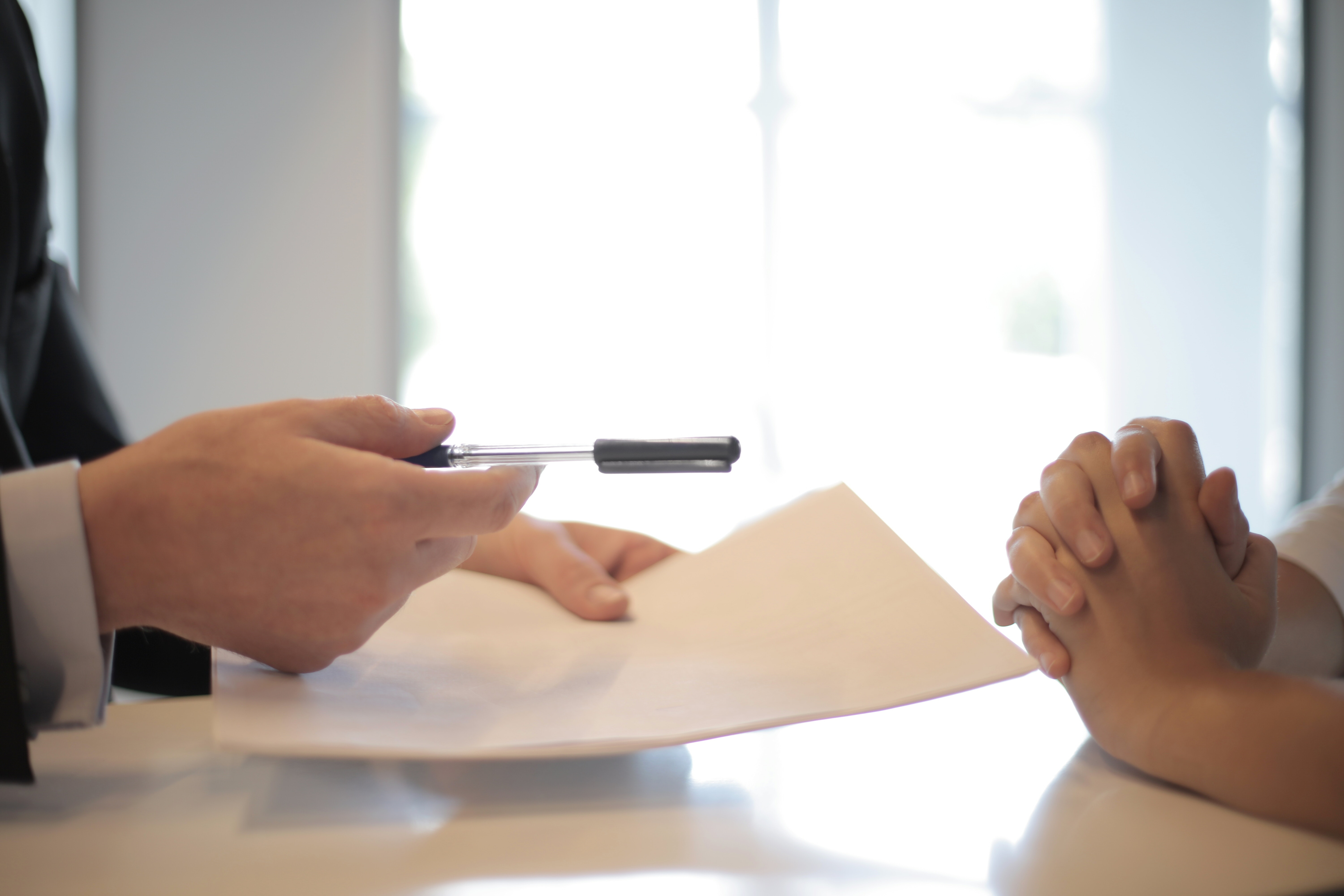 Person handing another person a document and pen with information about trading in their used vehicle