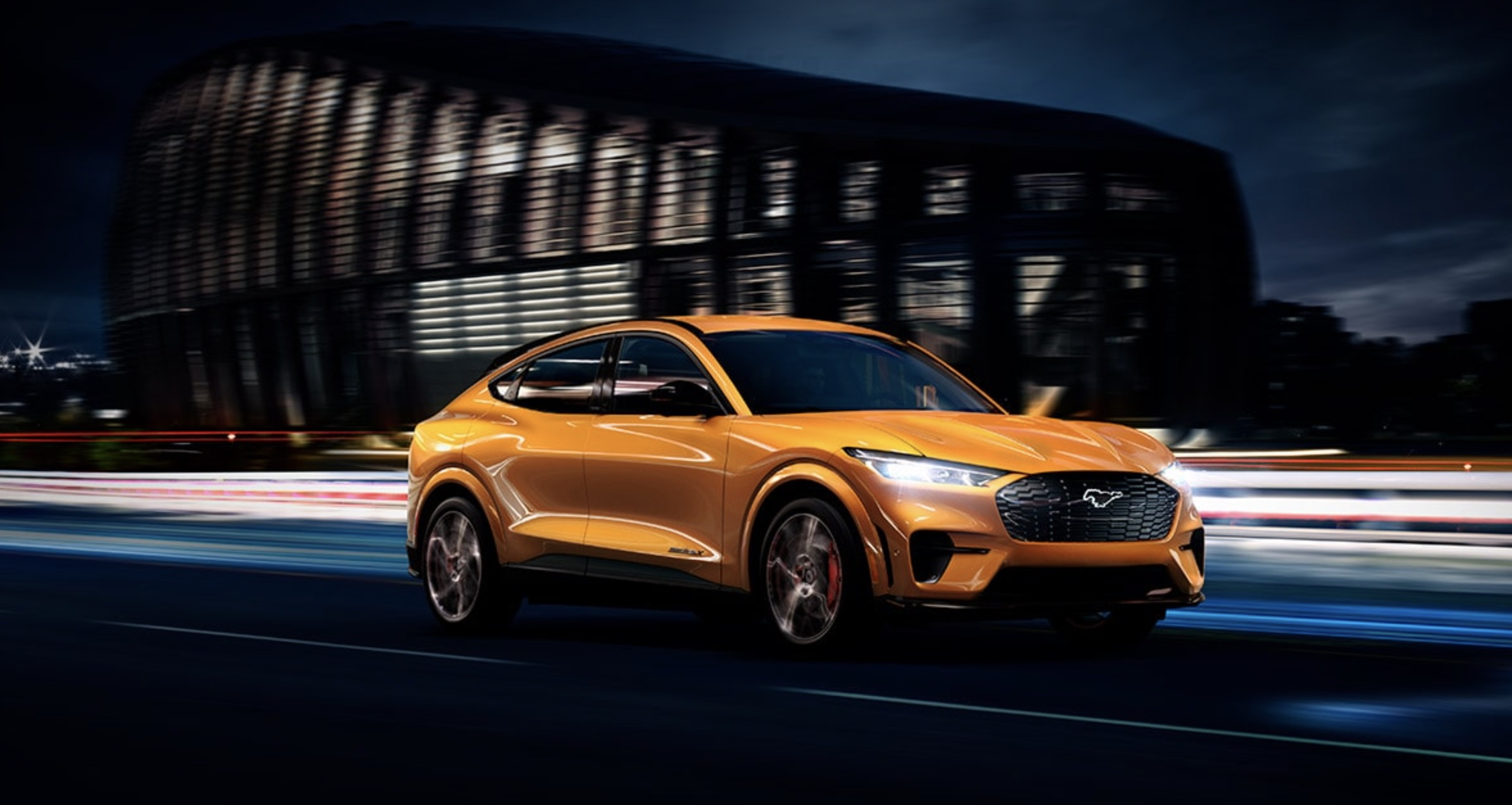 Orange 2021 Ford Mustang Mach-E driving on the road by a building