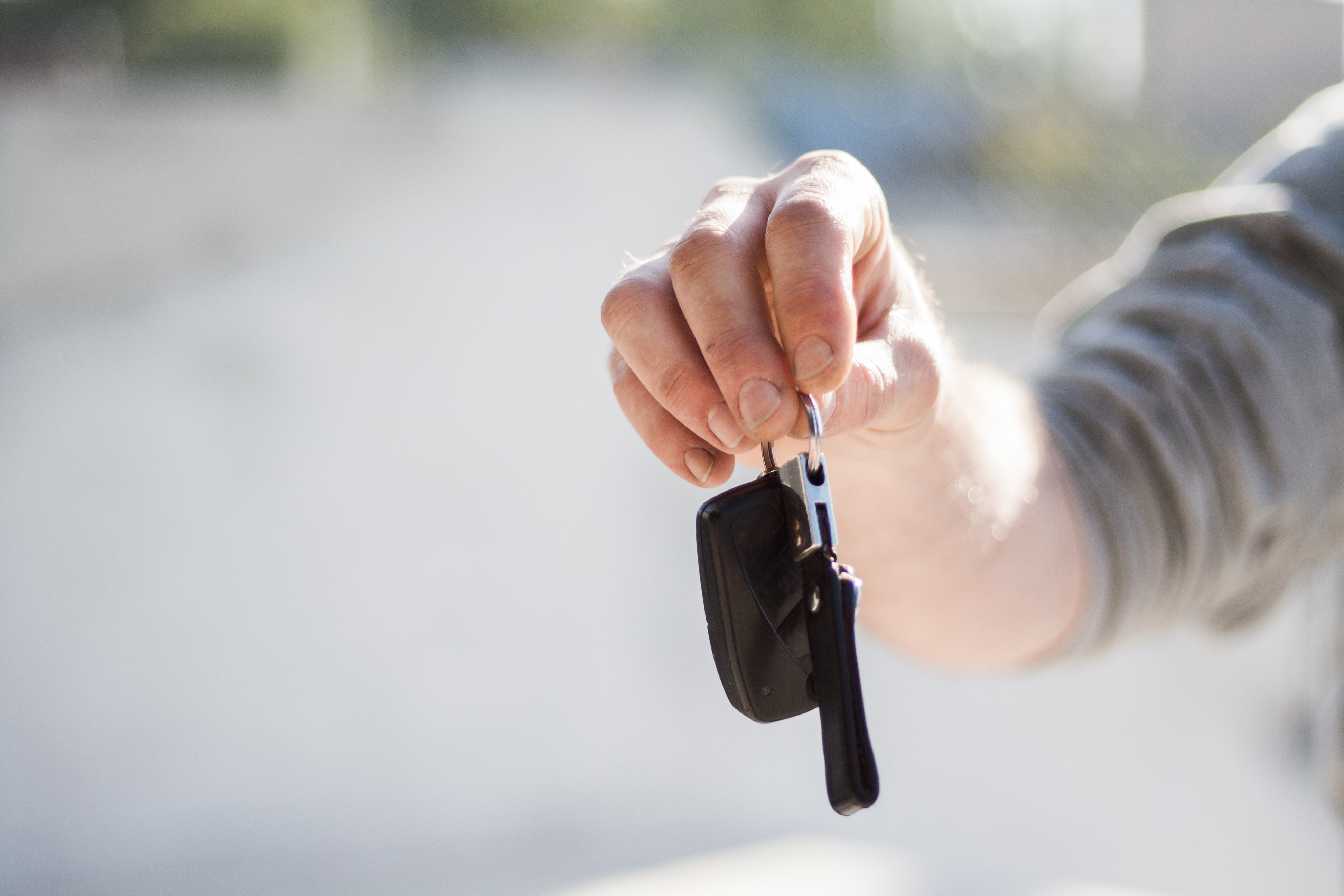 Person handing over keys to a used vehicle after a customer purchased it