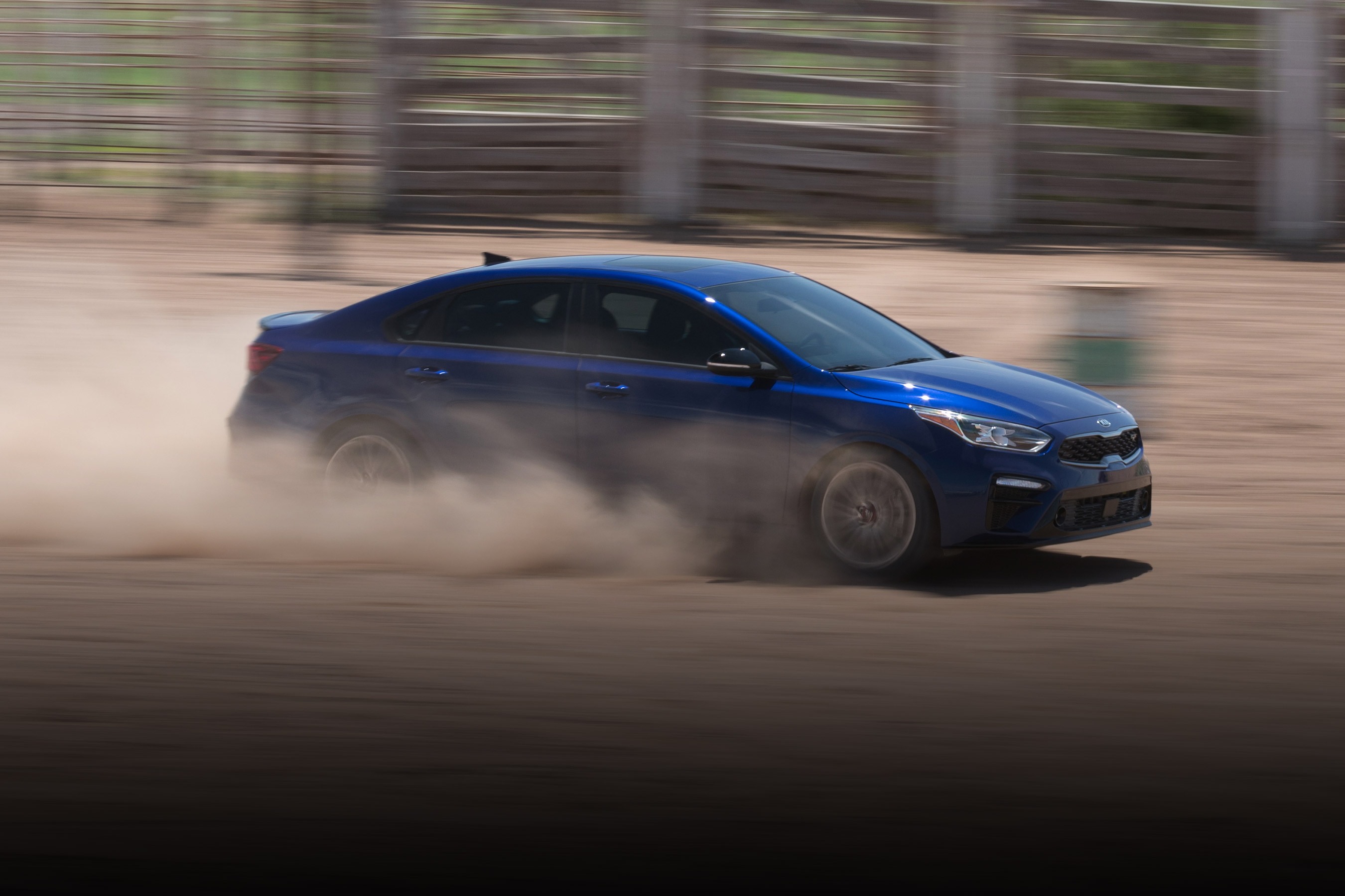 A Blue Kia Forte speeds with dirt kicking up under the wheels.