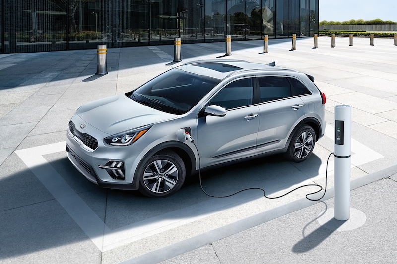 A Kia Niro plugged into a alternative fuel source in a parking lot.
