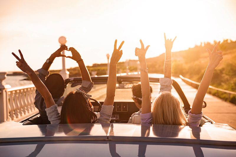 Four people in a convertible with their hands up at sunset