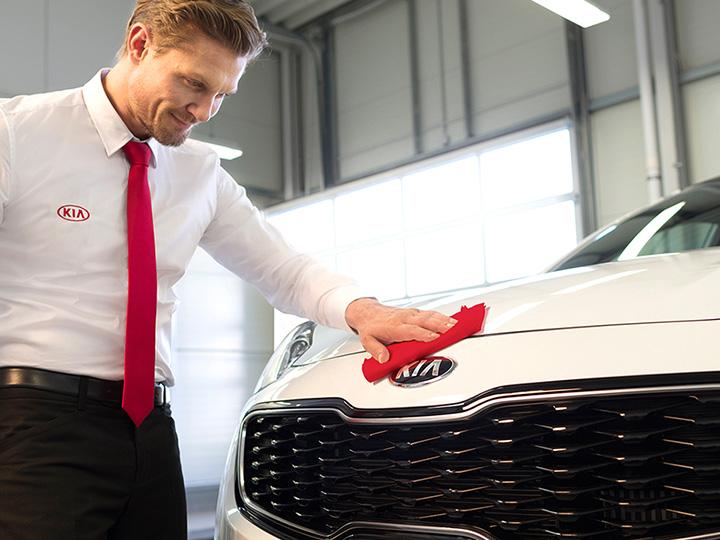 Kia service technician shining the car.