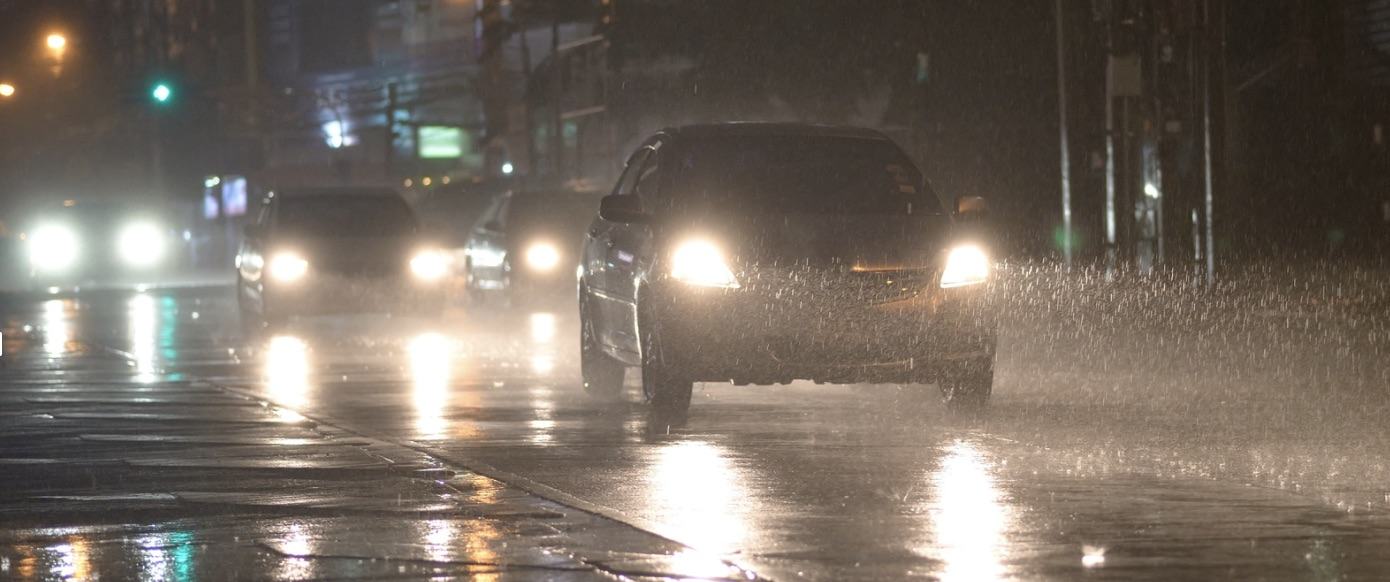 Car driving on the road with headlights showing the rain.