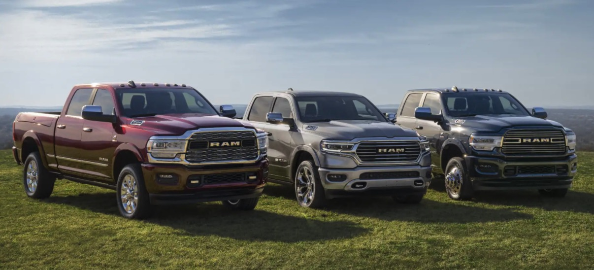 Three 2021 Ram pickup trucks lined up in a row parked on grass