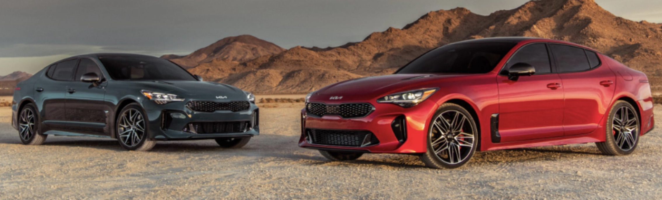 Photos of two Kia Stinger models in the background.