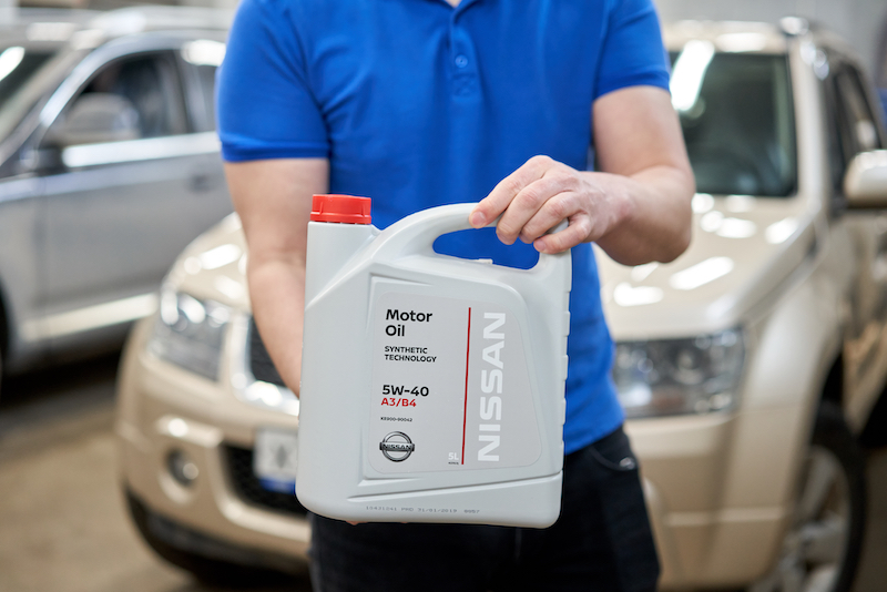 A service technician at a Nissan dealership holding a jug of oil to perform an oil change