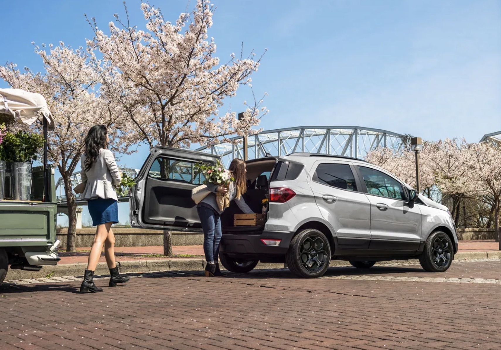 A silver 2021 Ford EcoSport parked while a woman is putting flowers in the trunk