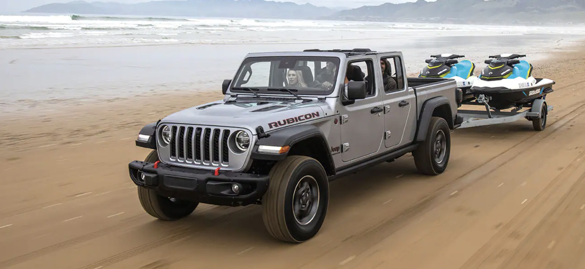 A gray 2021 Jeep Gladiator towing jet skis off-road on the beach by the mountains