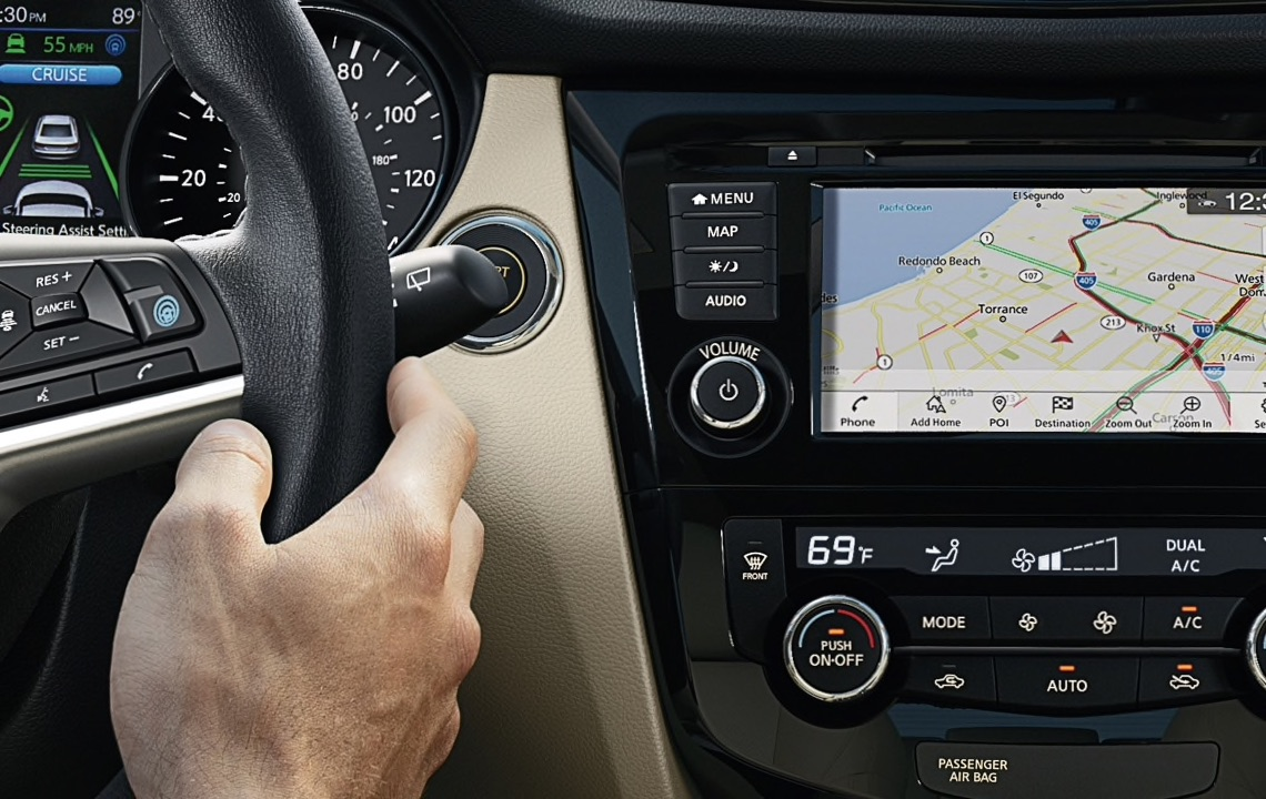 Up close image of a Nissan steering wheel and touch screen navigation system