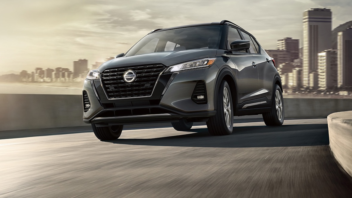 Grey 2021 Nissan Kicks driving down a road in the city