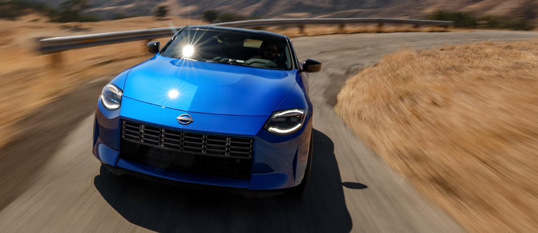 Blue Nissan Z Proto driving down a desert road