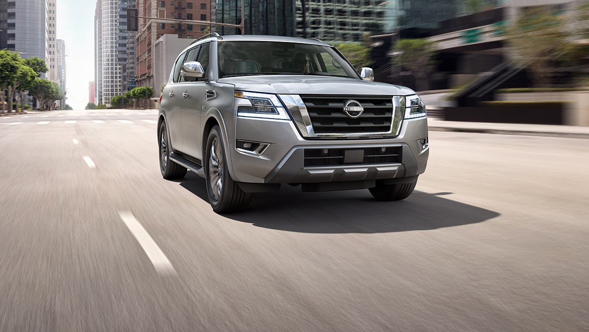 Silver new 2022 Nissan Armada driving down a sunny city street