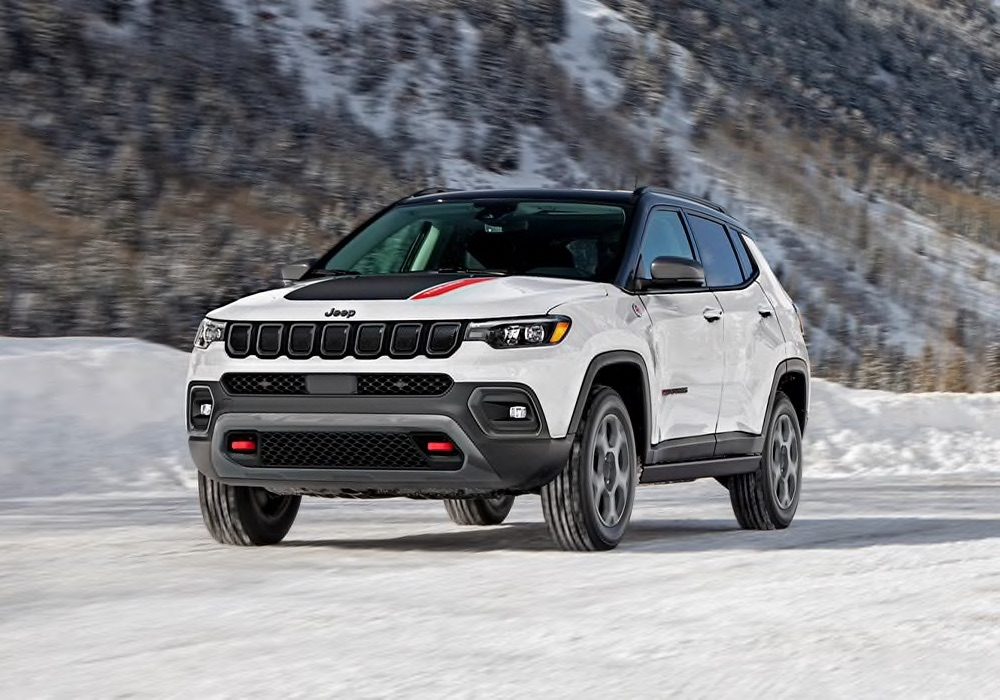 White 2022 Jeep Compass driving through the snow