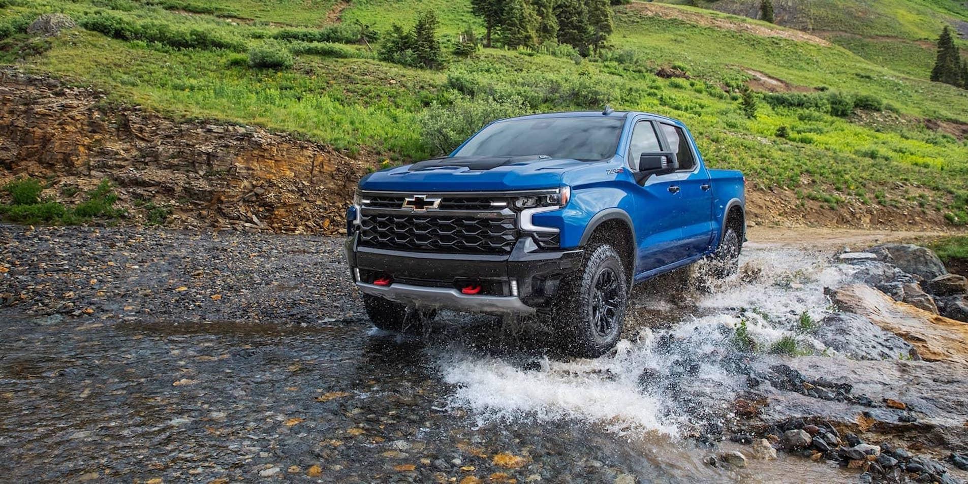 Blue Silverado Splashing Through Water on Road