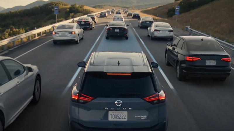 A 2021 Nissan Rogue Sport driving on the road around a lot of other vehicles